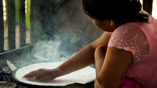 Native Ecuadorian woman cooking bread wit cassava flour